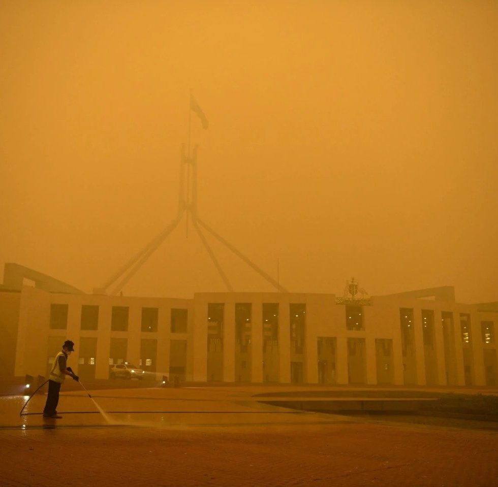 Amid an early-morning smoky haze, a man cleans the forecourt of Parliament House in Canberra, Australia, on Jan. 5. (Lukas Coch/Reuters)